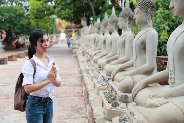 Porträt der asiatischen frau des schönen reisenden, die respekt zahlt und im alten tempel steht