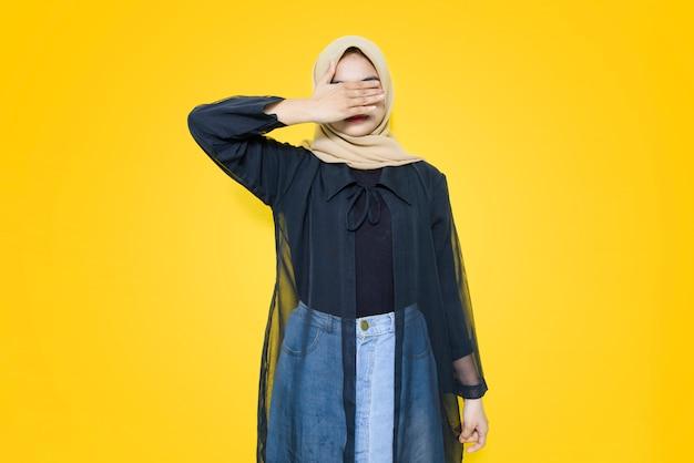 Porträt der asiatischen frau, die augen mit hand auf gelber wand bedeckt