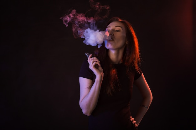 Porträt der asiatischen frau, die vape oder ecigarette im neonlicht am schwarzen hintergrund raucht.