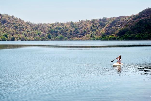 Porträt der asiatischen frau einen kajak auf dem see in satonda island schaufelnd