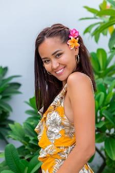 Porträt der asiatischen frau im gelben sommerkleid steht mit plumeria thai blume im haar und in den runden ohrringen