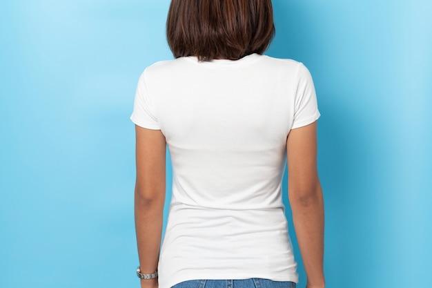 Porträt der asiatischen frau im leeren weißen t-shirt des modells auf blauem hintergrund