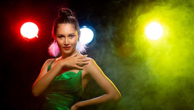 Porträt der asiatischen frau transgender tragen schönes grünes abend langes kleid, lächeln zur kamera über hintergrundbeleuchtung buntes gelb, rot, unschärfe mit rauch und posiert modeblick, studiobeleuchtung kopierraum