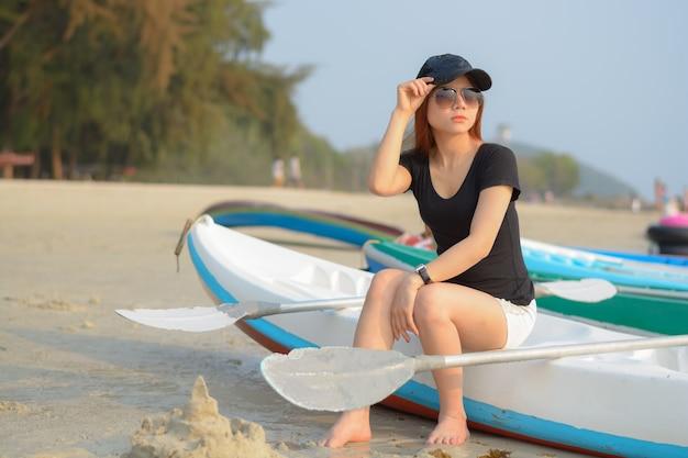 Porträt der asiatischen frau waer sonnenbrille mit kappen, die auf einem kajak sitzen