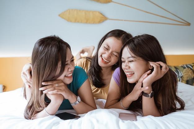 Porträt der asiatischen glücklichen freundschaft auf dem bett