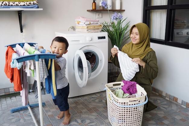 Porträt der asiatischen glücklichen mutter und des sohnes, die wäsche zusammen zu hause machen