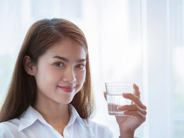 Porträt der asiatischen jungen frau der schönheit, die glas süßwasser hält. gesundheitswesen, getränk-schönheit, diät-konzept.