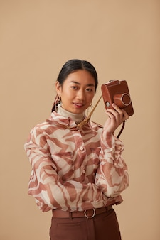 Porträt der asiatischen jungen frau, die alte fotofront hält, die front lokal auf beige wand lokalisiert betrachtet