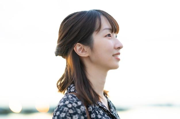 Porträt der asiatischen jungen frau, die am abend am meer steht