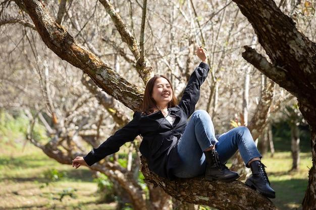 Porträt der asiatischen jungen frau, die pflaumenblütengarten im frühjahr genießt.