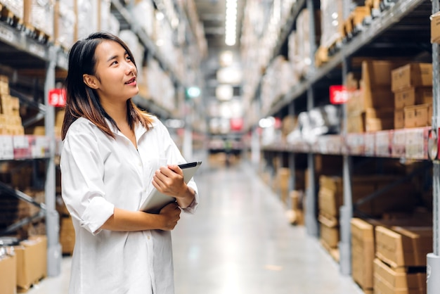 Porträt der asiatischen managerarbeiterin stehend und bestelldetails auf tablette