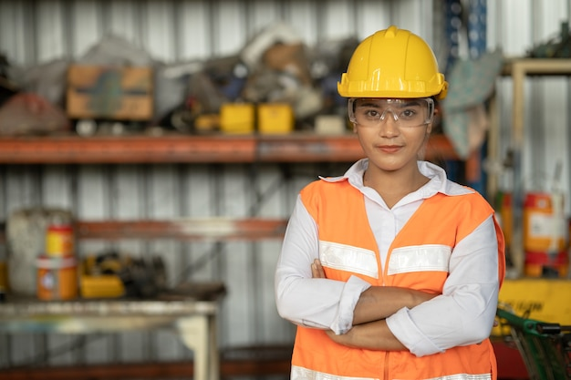 Porträt der asiatischen rasse der intelligenten arbeiterinnen mit stehendem lächeln des schützenden sicherheitsanzugs