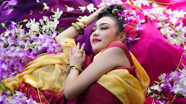 Porträt der asiatischen schönen langen frau des schwarzen haares mit dem traditionellen kostüm thailands, das durch blume liegt. reise- und lifestyle-konzept.