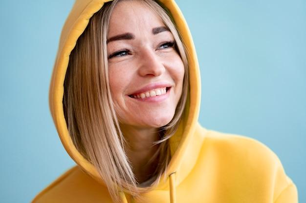 Porträt der asiatischen smileyfrau, die einen gelben kapuzenpulli trägt