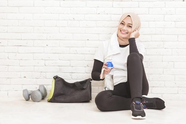 Porträt der asiatischen sportlichen frau, die auf dem boden sitzt, der nach dem training ruht
