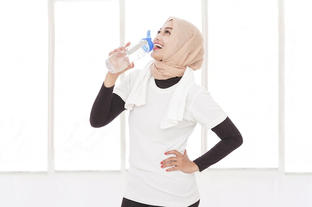 Porträt der asiatischen sportlichen frau, die mineralwasser nach dem training trinkt