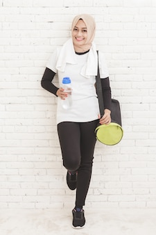 Porträt der asiatischen sportlichen frau, die sich gegen die wand lehnt, die nach dem training ruht