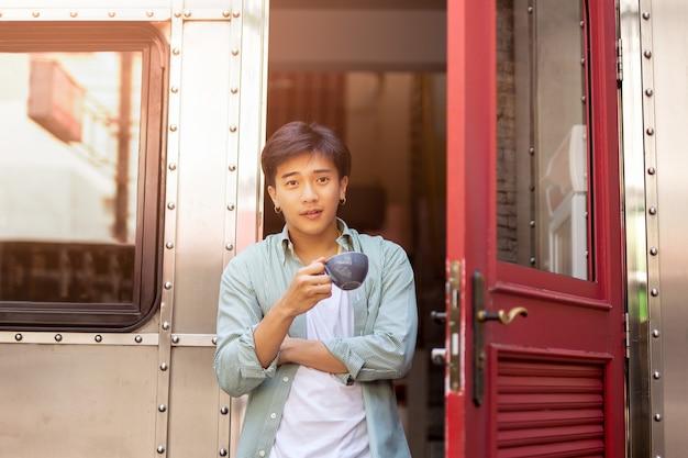 Porträt der asien-mannhand, die kaffeetasse hält, die auf haustür sich entspannt.