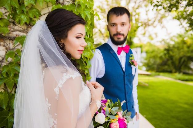 Porträt der atemberaubenden brünetten verschleierten braut mit einem bräutigam auf hintergrund