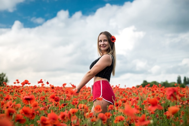 Porträt der atemberaubenden frau in sportbekleidung posiert, während sie in einem erstaunlichen mohnfeld an einem heißen sommerabend spazieren gehen, genießen sie die freiheit Premium Fotos