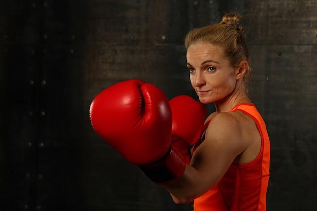 Porträt der athletischen frau in den roten boxhandschuhen