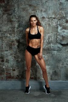 Porträt der athletischen kaukasischen attraktiven fit frau gekleidet in spitze und leggins, gegen steinmauerhintergrund sport, fitness, crossfit
