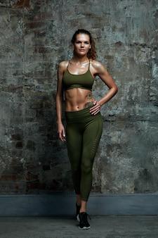 Porträt der athletischen kaukasischen attraktiven sitzfrau, die in der spitze und in den leggins gekleidet wird, gegen steinmauerhintergrund. sport, fitness, crossfit.
