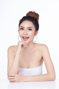 Porträt der attraktiven asiatischen frau, die das lächeln auf weißem hintergrund sitzt.