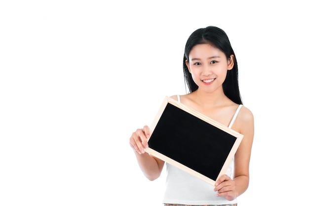 Porträt der attraktiven asiatischen jungen frau mit schönheitshaut und gesicht, die leere tafel halten.