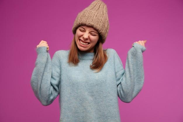 Porträt der attraktiven, aufgeregten jungen frau mit brünettem langem haar. trägt einen blauen pullover und eine strickmütze. schielen und lächeln. hören sie frohe nachrichten über lila wand