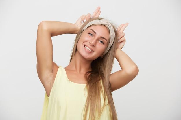 Porträt der attraktiven blauäugigen blonden frau, die ohren mit erhobenen händen nachahmt und kamera positiv betrachtet, während über weißem hintergrund im gelben hemd aufwirft