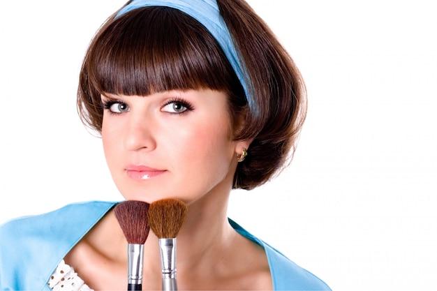 Porträt der attraktiven brunetfrau im blauen kleid mit zwei make-upbürsten lokalisiert auf weißem hintergrund
