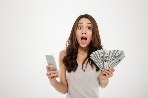 Porträt der attraktiven brunettefrau 30s, die viele gelddollarwährung unter verwendung ihres smartphone, seiend froh über weiß gewinnt