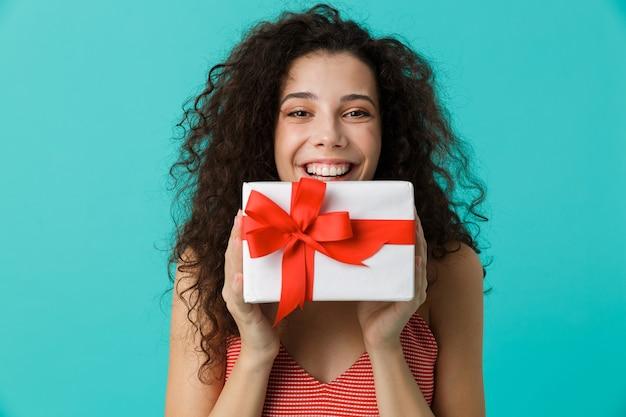 Porträt der attraktiven frau, die freizeitkleidung hält, die geschenkbox hält, lokalisiert über blaue wand