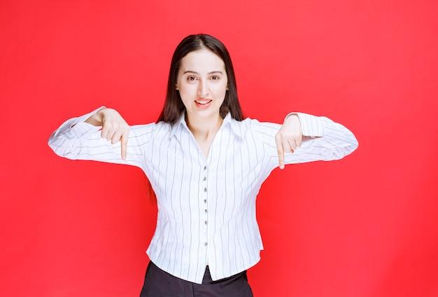 Porträt der attraktiven frau, die mit den fingern nach unten steht und zeigt.