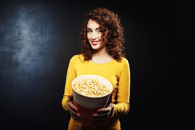 Porträt der attraktiven frau, die popcorn mit fröhlichem lächeln behandelt