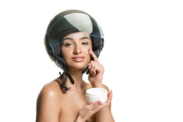 Porträt der attraktiven frau im motorradsturzhelm auf weißer wand. beauty-, haut- und gesichtsschutzkonzept
