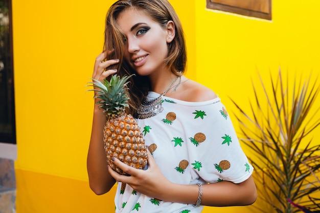 Porträt der attraktiven frau im pint-t-shirt in den sommerferien, die ananas, fruchtdiätentgiftung, gebräunte haut, leuchtend gelben hintergrund halten