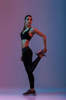 Porträt der attraktiven frau in voller länge, die schwarzen trainingsanzug trägt, der gymnastik tut und ihre beine streckt, lokalisiert über lila wand