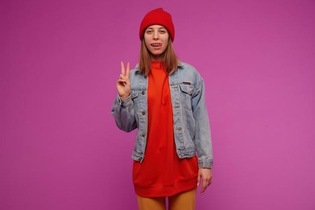 Porträt der attraktiven frau mit dem brünetten langen haar. trägt jeansjacke, gelbe hose, roten pullover und hut. friedenszeichen und zunge über lila wand zeigend