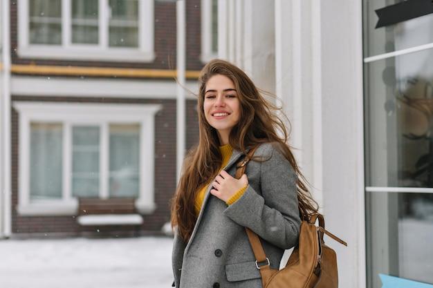 Porträt der attraktiven frau mit dem langen braunen haar, das rucksack trägt und sanft lächelt. foto der raffinierten kaukasischen dame in der grauen jacke, die aufwirft