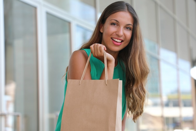 Porträt der attraktiven frau mit einkaufstasche in der hand