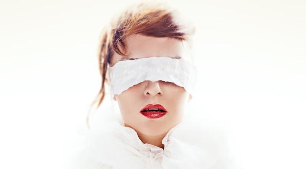 Porträt der attraktiven frau mit verbundenen augen mit weißem papierband