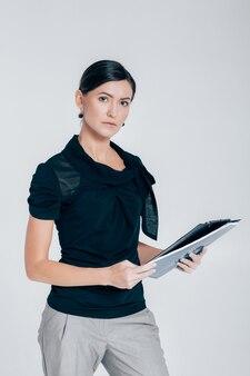 Porträt der attraktiven geschäftsfrau, die einen ordner mit dokumenten auf einem grauen hintergrund hält