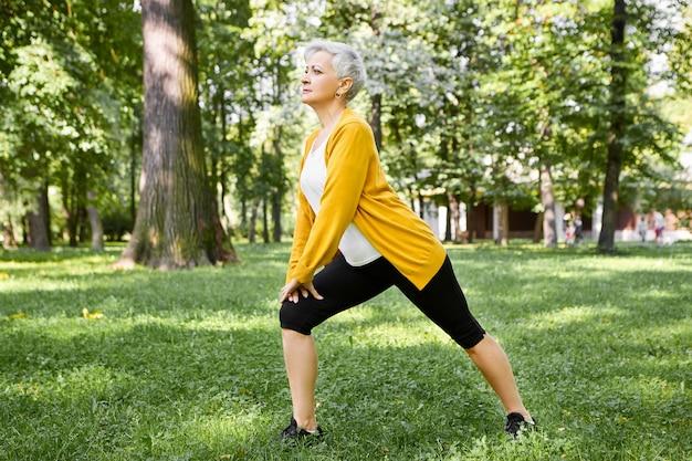 Porträt der attraktiven gesunden sechzigjährigen frau, die auf einem bein steht und sich in pilates-haltung ausdehnt. grauhaarige ältere frau in der sportbekleidung, die seitliche ausfallschritte auf gras im stadtpark am sonnigen tag tut