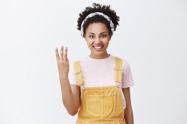 Porträt der attraktiven glücklichen afroamerikanischen weiblichen frau im gelben overall und im stirnband, das nummer drei mit den fingern zeigt und breit über graue wand lächelt