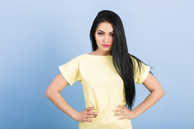 Porträt der attraktiven jungen brünetten frau im gelben kleid auf blau