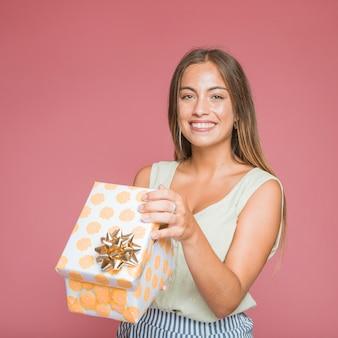 Porträt der attraktiven jungen frau, die eine offene geschenkbox gegen farbigen hintergrund hält