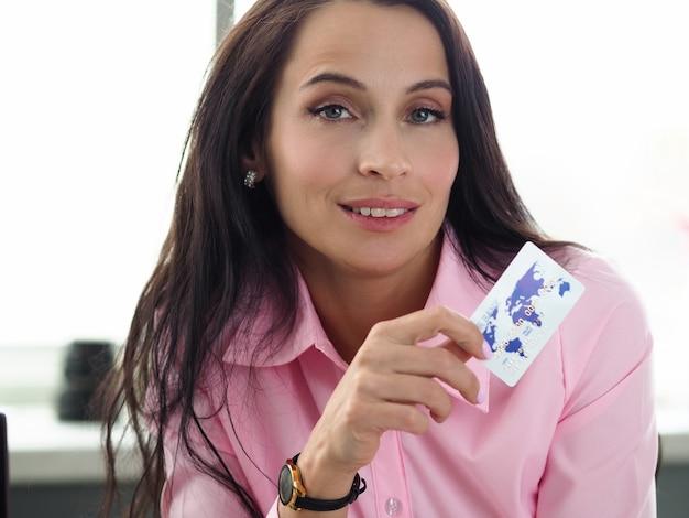 Porträt der attraktiven jungen frau, die weiße plastikkreditkarte hält. hübsche frau in der rosa bluse, die drinnen aufwirft. moderne technologie. online-zahlung für einkaufskonzept