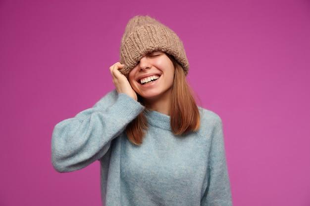 Porträt der attraktiven, jungen frau mit dem brünetten langen haar. trägt einen blauen pullover und eine strickmütze. zieht hut über auge und lächelt isoliert über lila wand